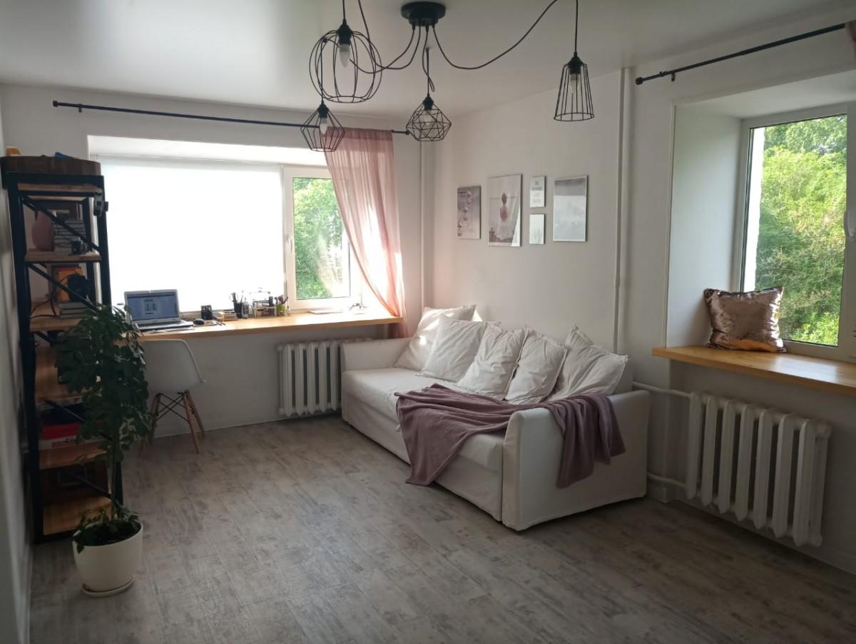 Простой и светлый дизайн зала с двумя окнами, со шкафом и рабочей зоной на подоконнике