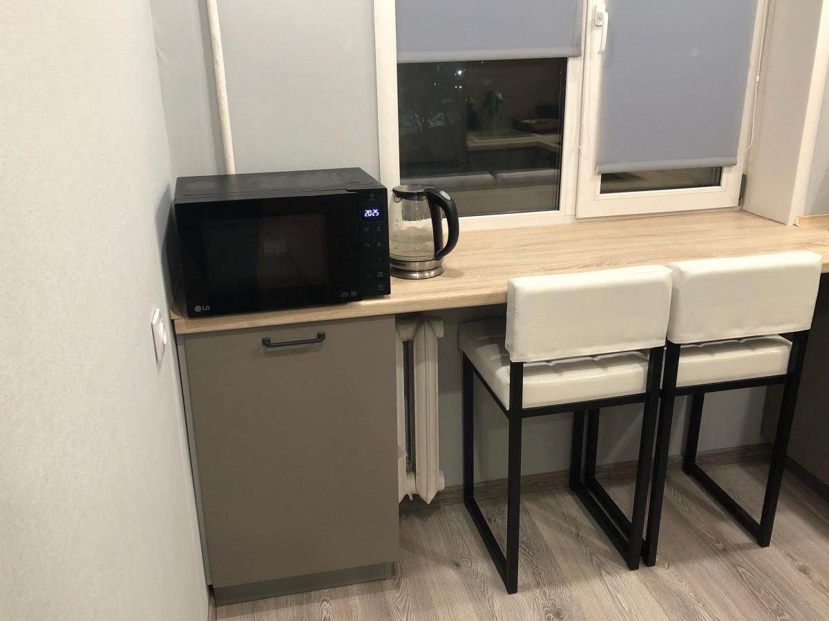 Современная Г-образная бело-серая кухня со столом вместо подоконника и столешницей под дерево
