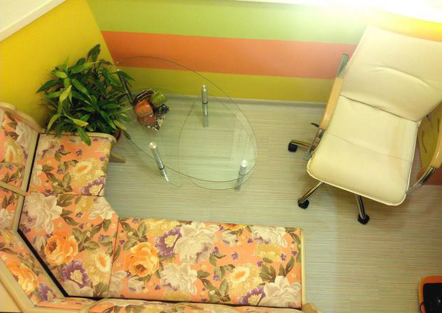 Яркий балкон с диванчиком для отдыха и столом с компьютером для работы